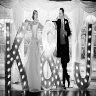 wedding couple in front of light up initials K&J