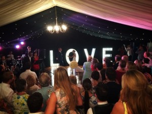 Fairground lights on wedding stage with dancing couple