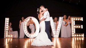 wedding couple and bridesmaids pose in front of light up love letters
