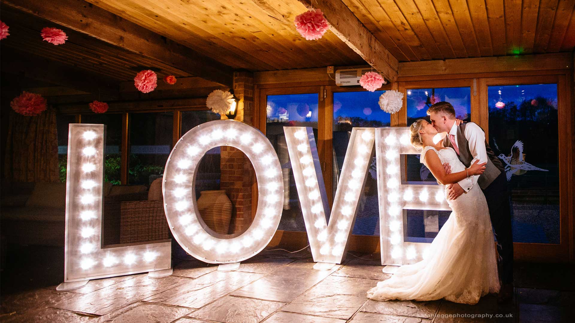 bride and groom dancing in front of lightbulb letters