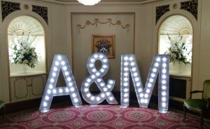 light up wedding initials set up at plaisterer's hall with flowers