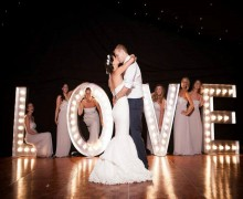 wedding couple in front of light Up love sign
