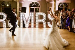 bride and father in front of mr and mrs light up sign