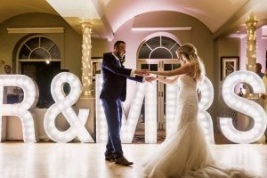bride and groom dancing in from of light up sign