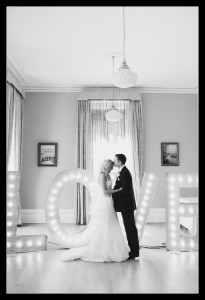 couple in front of light up love sign