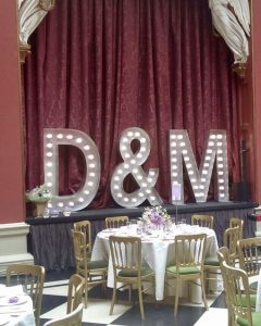 Wedding initials set up at Hampton Court House with red curtain backdrop